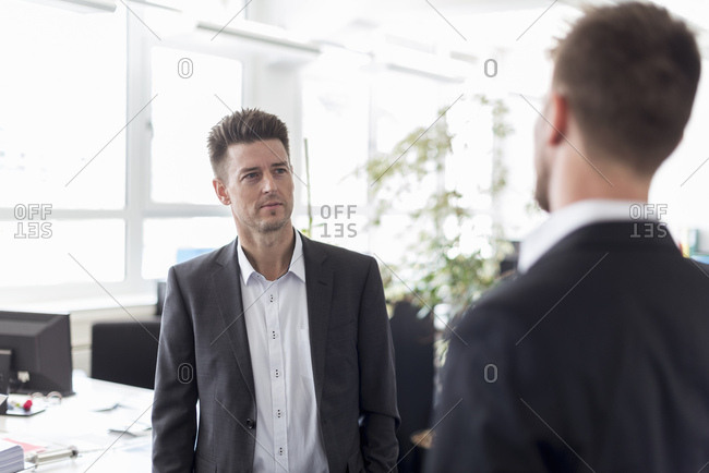 Two businessmen standing in office- discussing solutions