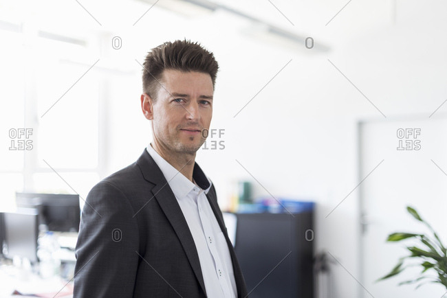 Portrait of a successful businessman standing in office- looking serious