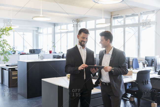 Two businessmen standing in office- discussing solutions- using digital tablet