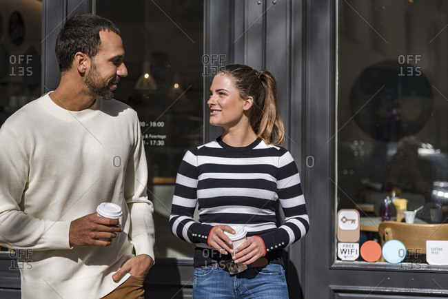 Man and woman holding takeaway cups outside a cafe talking