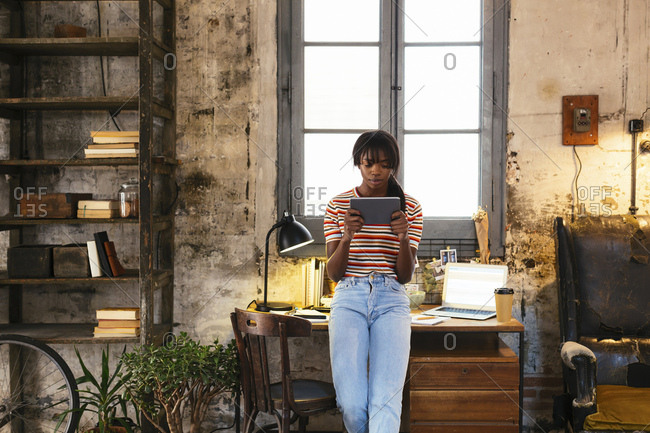 Young woman standing in front of desk in a loft using tablet