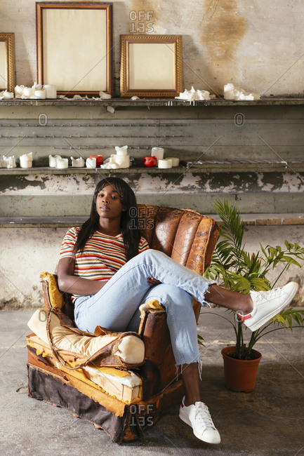 Portrait of cool young woman sitting on an old leather chair in a loft