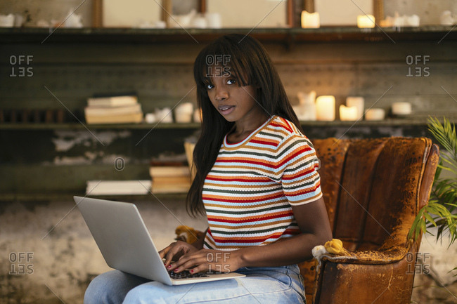 Portrait of young woman sitting on an old leather chair working on laptop in a loft