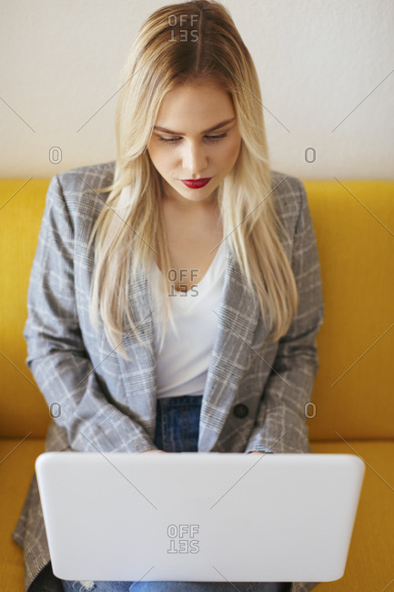 Businesswoman sitting on yellow couch- using laptop