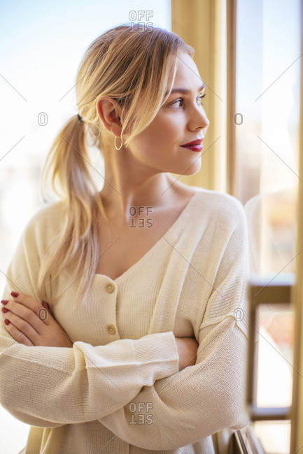 Blonde woman looking out of window