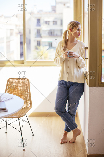 Blonde woman with cup of coffee looking out of the window