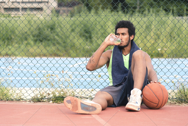 Young basketball player drinking from water bottle