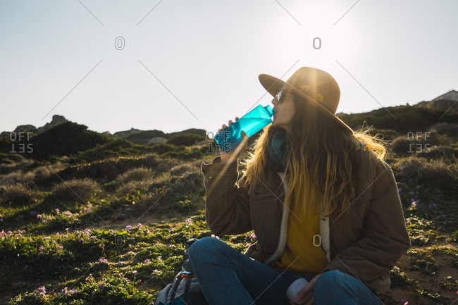 Italy- Sardinia- woman on a hiking trip having a break drinking from water bottle