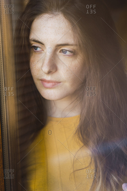 Portrait of pensive young woman with long brown hair looking out of window