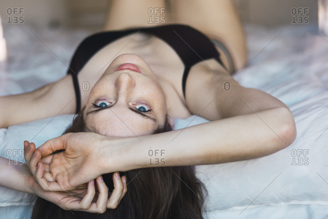Young woman in underwear lying on bed