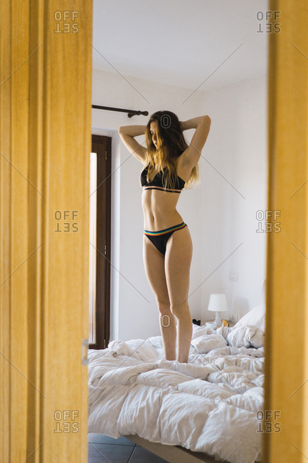 Young woman in underwear standing on bed with hands behind head