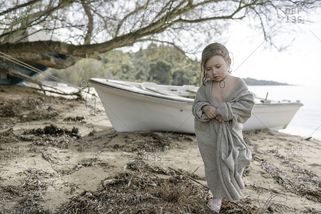Sad little girl wrapped in oversized cardigan standing on the beach