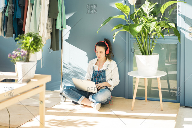 Young freelancer sitting on the floor in her studio using laptop and headphones