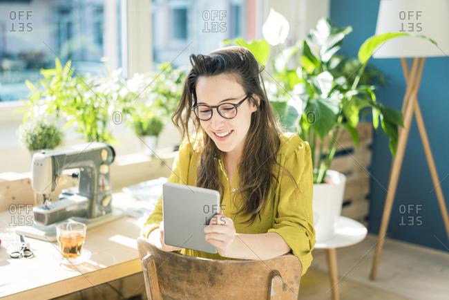 Portrait of smiling fashion designer sitting in her studio using tablet