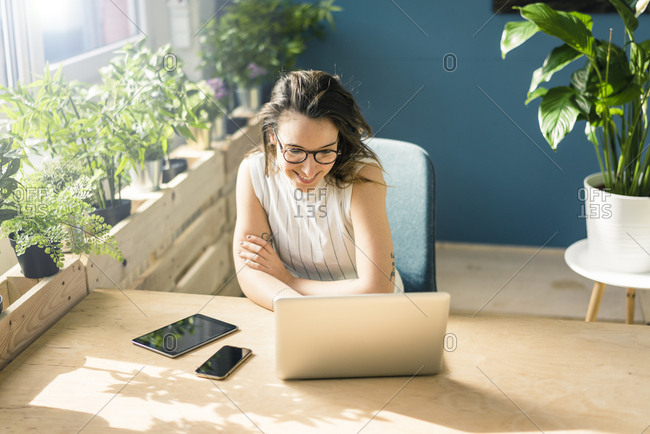 Smiling freelancer sitting at desk in loft looking at laptop