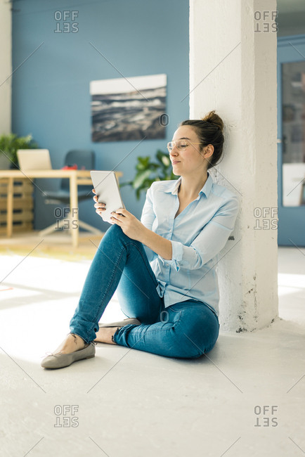 Young freelancer sitting on the floor in her studio using tablet