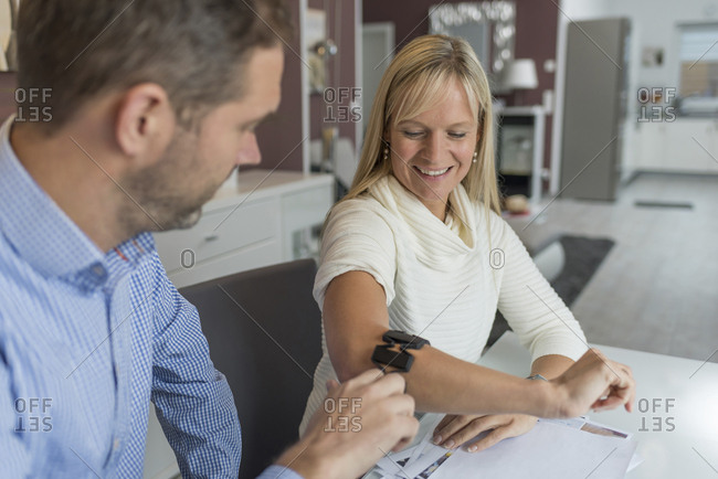 Man and smiling woman with wearable at her arm at desk