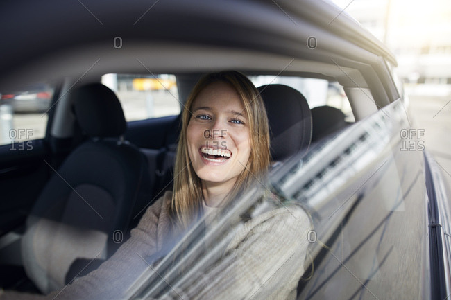Portrait of laughing young woman sitting in car