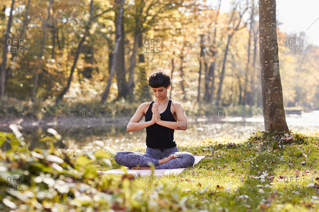 Mid adult woman in forest practicing yoga- meditation