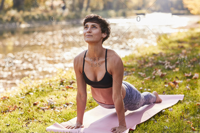 Mid adult woman in forest practicing yoga- cobra pose