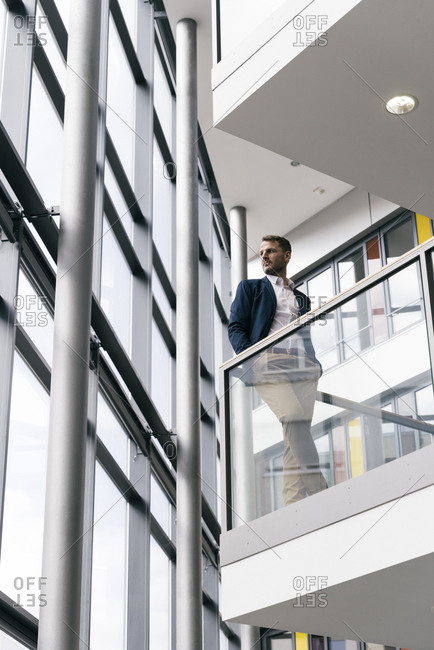 Businessman in office building looking out of window