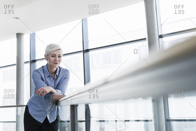 Portrait of woman in office building leaning on railing