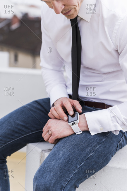 Businessman sitting outdoors using smartwatch