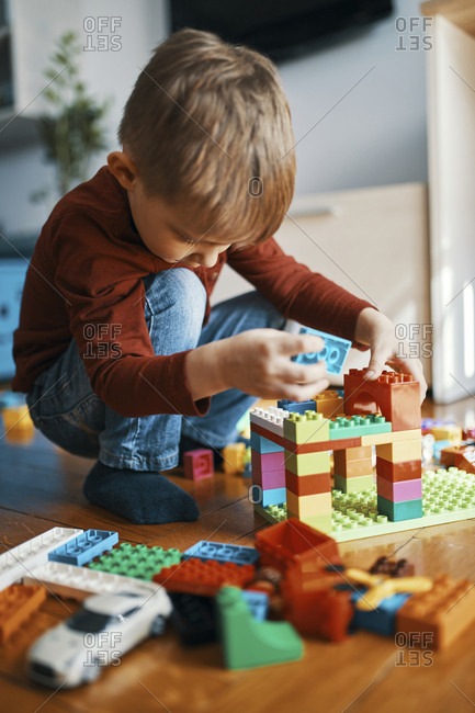 Little boy playing with building bricks on the floor at home