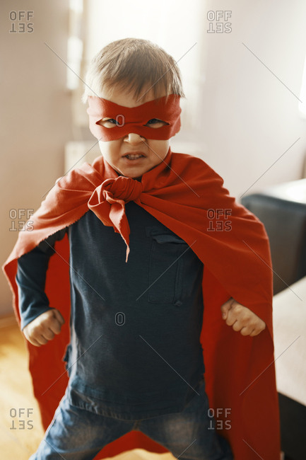 Portrait of little boy dressed up as a superhero at home