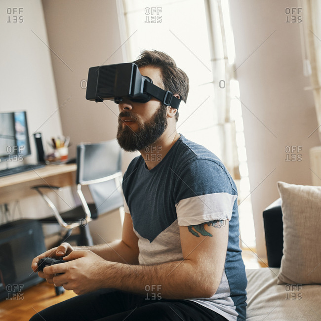 Man wearing virtual reality glasses at home playing computer game