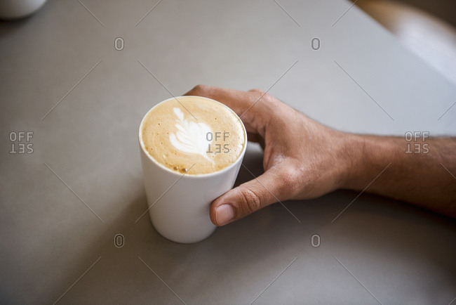 Hand and cup of cappuccino in a cafe