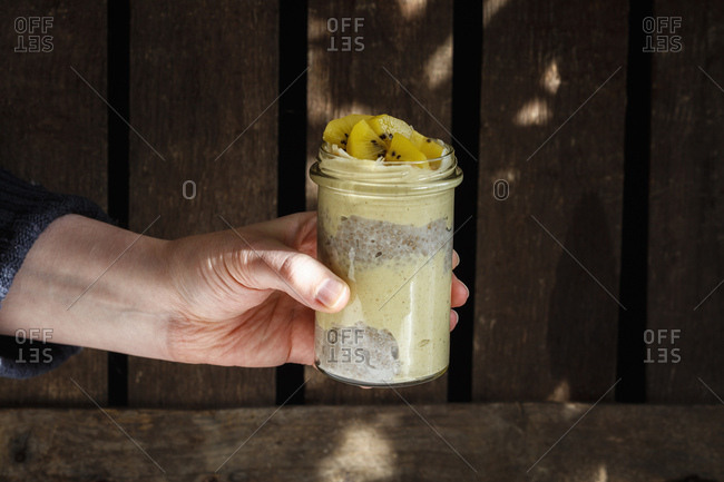 Man's hand holding glass of chia pudding with mango smoothie garnished with kiwi