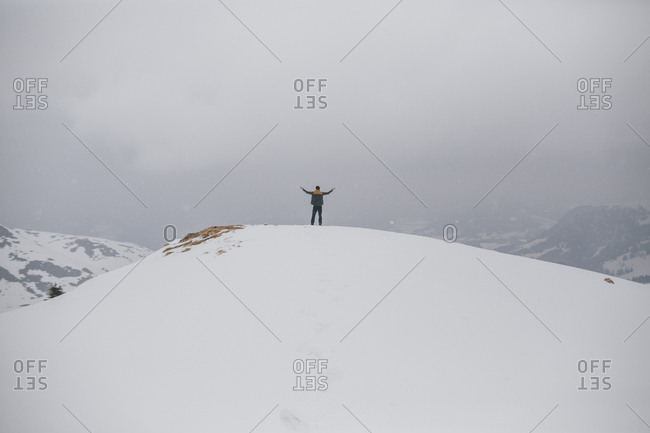 Austria- Kitzbuehel- back view of happy man enjoying snow-covered landscape