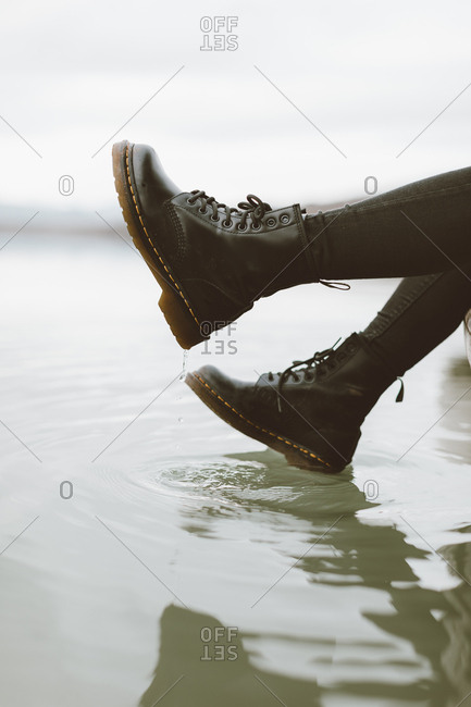 Woman wearing black boots touching water surface of lake- partial view