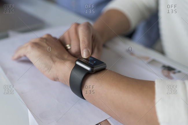 Woman's hand adjusting smartwatch at desk