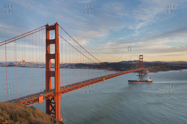 USA- California- San Francisco- Ship crossing Golden Gate Bridge in the evening