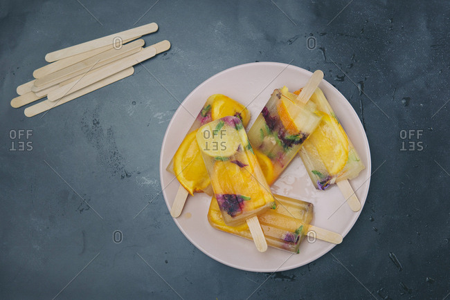 Homemade orange and lemon popsicles with edible flowers on plate