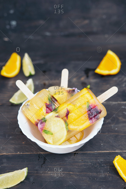 Bowl of homemade orange and lemon popsicles with edible flowers