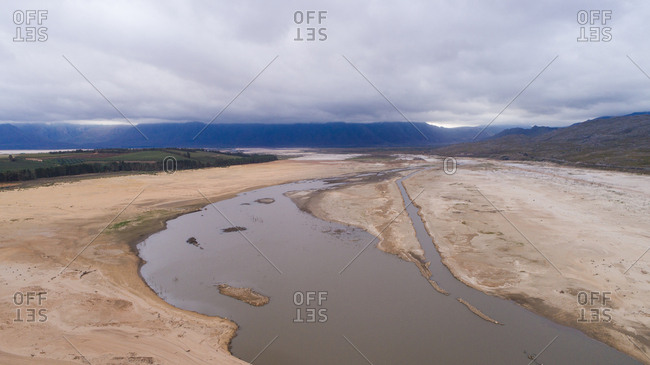 Aerial image over a dry Theewaterskloof dam during the worst drought in decades in the Western Cape of South Africa with massive patches of barren earth exposed