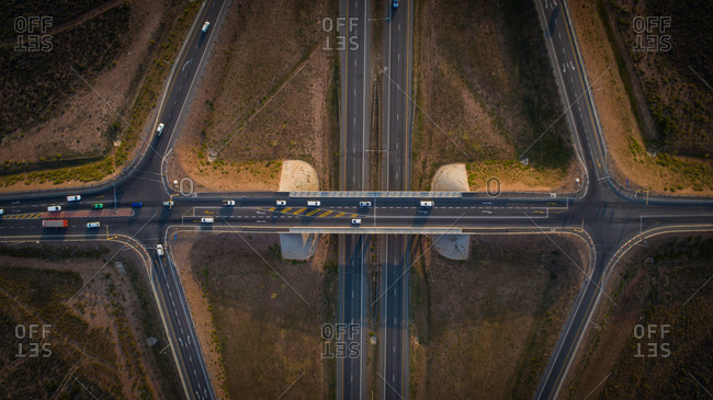 Aerial view over a highway interchange during peak hour traffic.