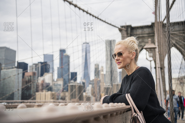 Young blonde woman standing at railing of Brooklyn Bridge looking out at the view