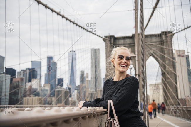 Young blonde woman looking over shoulder smiling standing at railing on Brooklyn Bridge