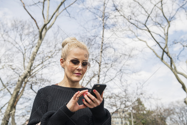 Low angle view of young blonde woman checking smartphone while walking through park