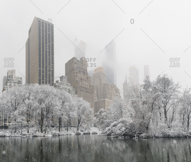 Tall buildings shrouded in mist seen from Central Park as snow falls in New York City