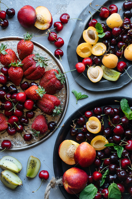 Top down view of several dishes overflowing with fresh summer fruits and berries