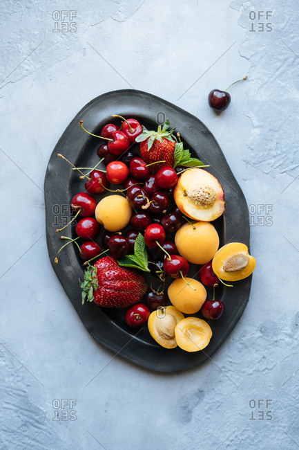 Top down view of nectarines, apricots, strawberries and cherries piled onto platter on light background