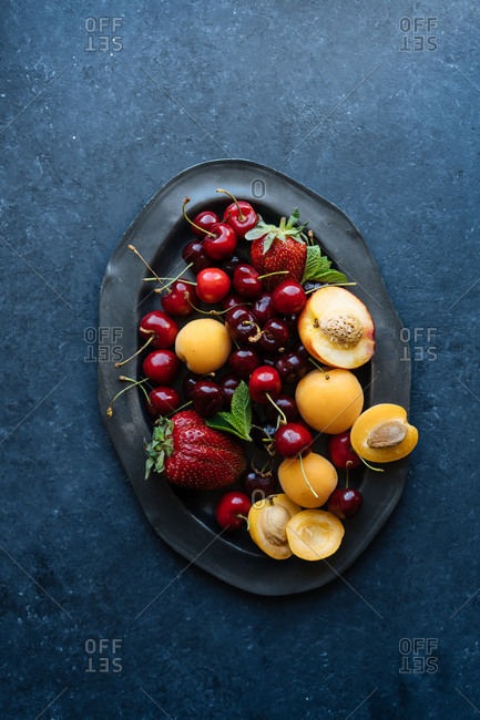 Top down view of nectarines, apricots, strawberries and cherries piled onto platter on dark background
