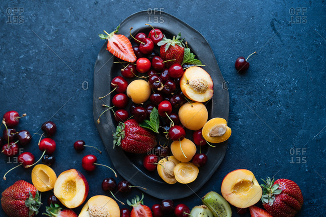 Top down view of selection of fresh summer fruits and berries overflowing from platter onto dark table top