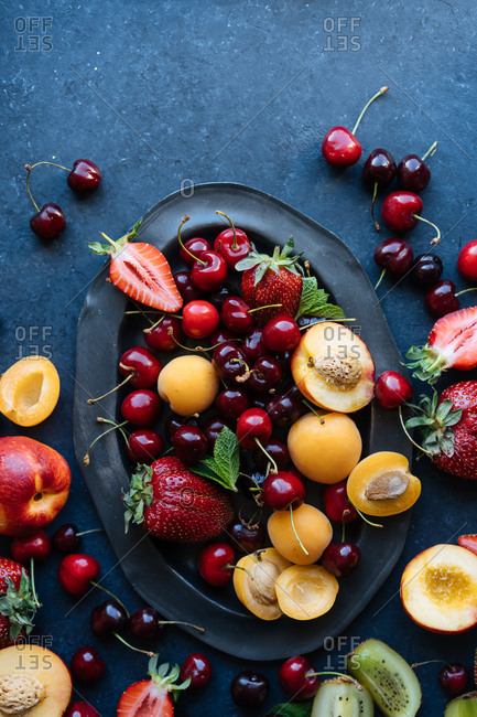 Looking down on variety of fresh summer fruits and berries overflowing from dark platter onto dark table top