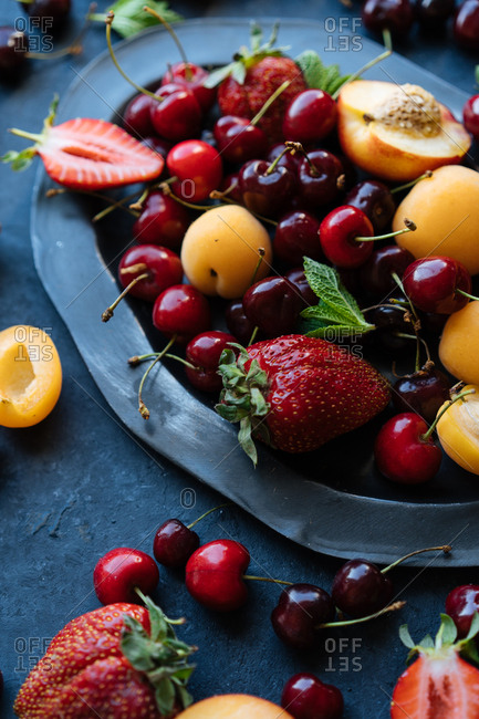 High angle view of variety of colorful summer fruits and berries on dark platter and table